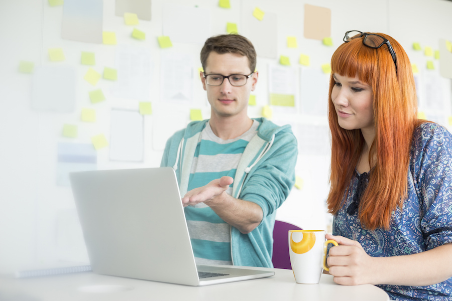 Businessman showing something to female colleague on laptop in creative office